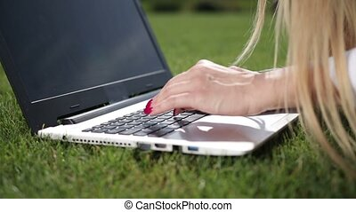 Businesswoman hands typing on a laptop outdoor