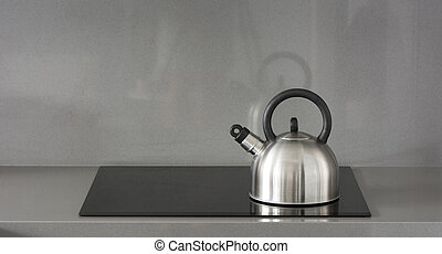 Steel teapot on induction stove in kitchen
