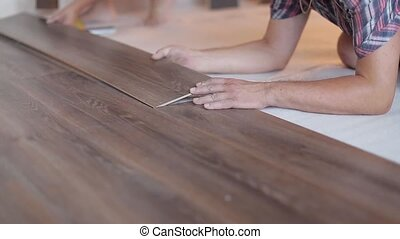 Worker puts the board flooring laying laminate flooring