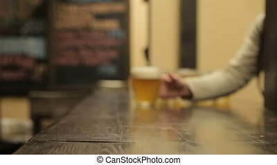 Man catches a beer mug on the table in the pub