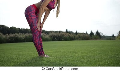 Fit young woman doing standing forward bend - Fit young...