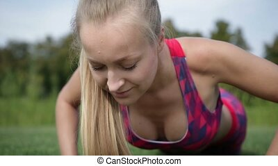 Sporty fit woman exercising by doing push-ups - Close up of...