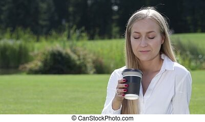 Cheerful young woman drinking coffee outside - Cheerful...