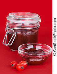 Rose hip jam and fruits over red background, also rose haw...