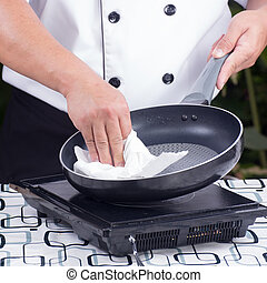 chef wiping the pan before cooking