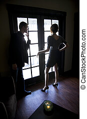 Young couple standing by window in dark room - Silhouette of...