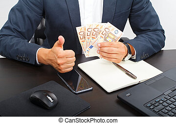 Success in business - Office manager holding money in his...