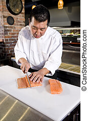 Japanese chef slicing raw fish for sushi - Japanese chef in...