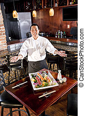 Japanese restaurant chef presenting sushi platter - Chef in...