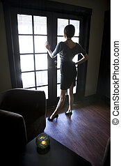 Young woman looking out window in dark room