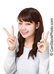 young Japanese woman showing a victory sign - studio shot of...