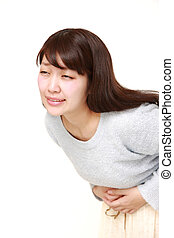 young Japanese woman suffers from stomachache - studio shot...