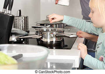 Small girl salting food with her father in the kitchen