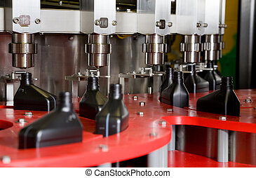 Fill line - Oil is dispensed into quart bottles at a...