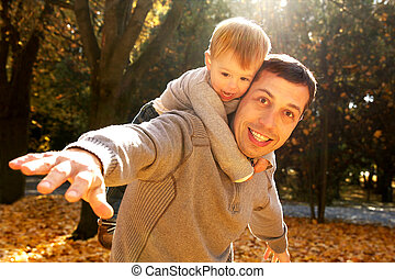 a little boy with his father in autumn outdoors