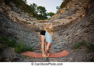 man in blue shirt doing second step of surya namaskar,...