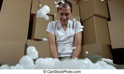 Man throwing soft polystyrene pieces. Shockproof packaging...