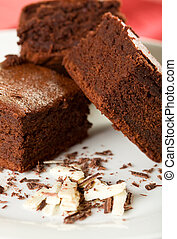 Three Chocolate Brownies on a white plate with dark and...