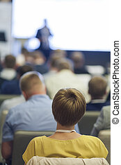 People at the Business Conference Listening to the Speaker Standing in Front of a Big Board on Stage.