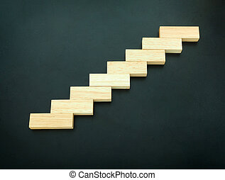 Wood block stacking as step stair on black background. Business or life concept for growth success process.