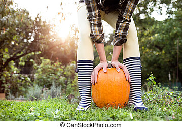 Unrecognizable woman in striped rubber boots holding orange...