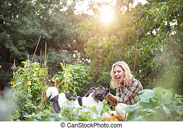 Beautiful blond woman with dogs in green garden - Beautiful...