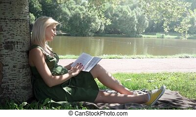 Pregnant woman reading a book sitting on the grass