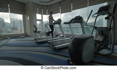Woman exercising on treadmill in the gym - Steadicam shot of...