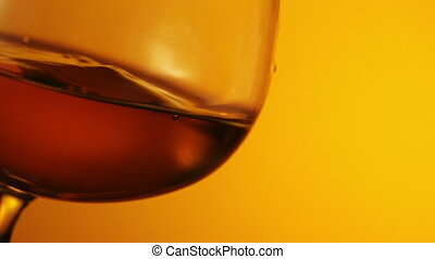 The glass with splashes cognac on black background