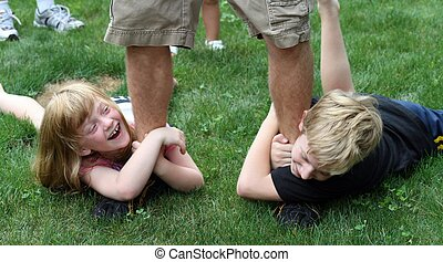 Kids dragging on feet of boy - two cousins (boy and girl)...