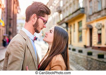 Young fashion elegant stylish couple posing on streets of europe