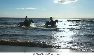 Beautiful young women horse riding at a beach. Enjoying...