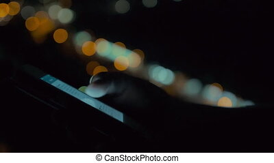 Using smart phone on background of night city lights -...