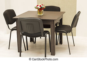 four chairs stand near the table