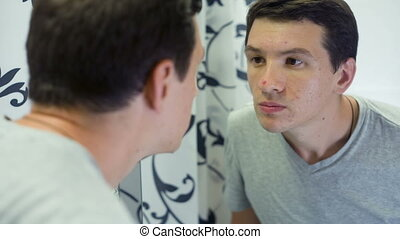 Man with Problem Skin in front of the mirror - depressed man...