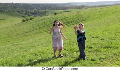 Two kids catch the soap bubbles on the hill