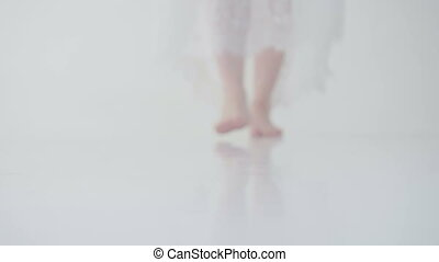 female bare feet going forward on a white floor. woman in a...