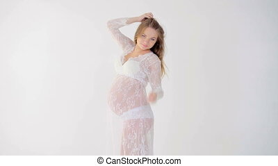pregnant woman dancing on white background - Young pregnant...