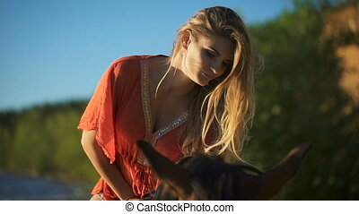 Close-up a sexy beautiful young woman riding a horse at a...