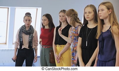 Women are preparing fashion show in model school. Talking...