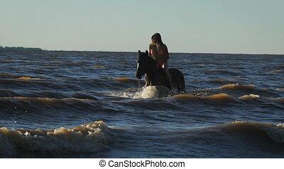 A young beautiful blonde woman in bikini in the sea riding a...