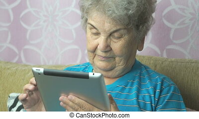 Aged woman using a computer tablet sits on a beige sofa at...