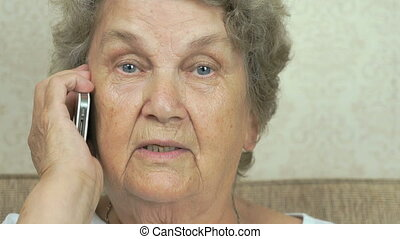 The old woman talking on a mobile phone at home - The old...