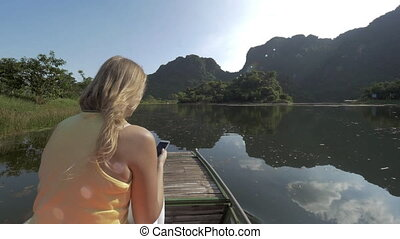 Woman traveler with mobile taking shots during Trang An boat...