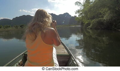 View of blond woman with camera on the boat. Excursion in...