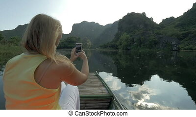 Female tourist taking photos with cell during boat in Trang An, Vietnam
