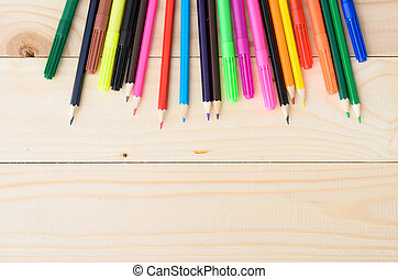Colored pencils on a wooden board with copy space for text
