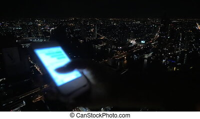 Girl typing message on cellphone on night city background -...