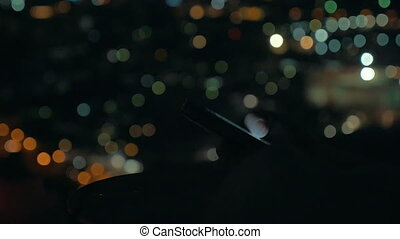 Woman with cellphone on city lights background at night -...