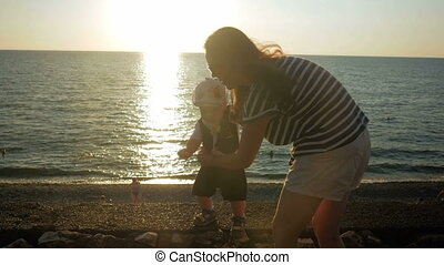 Young mother walking with cute baby on the oceanfront at sunset. The baby is still very poor, and my mother runs it holds. The concept of the first steps in life